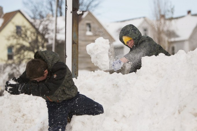 Children play in a snow pile in Buffalo, New York, November 20, 2014. Fresh snow fell on Thursday in snowbound western New York state, where longtime residents described the blast of winter weather as the worst in memory.  REUTERS/Lindsay DeDario