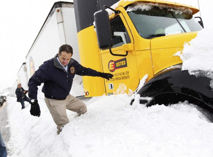 New York Governor Andrew Cuomo climbs over snow piled on the highway after talking with a stranded trucker on interstate I-190 while surveying an area in West Seneca. SHARON CANTILLON/BUFFALO NEWS/POOL/REUTERS