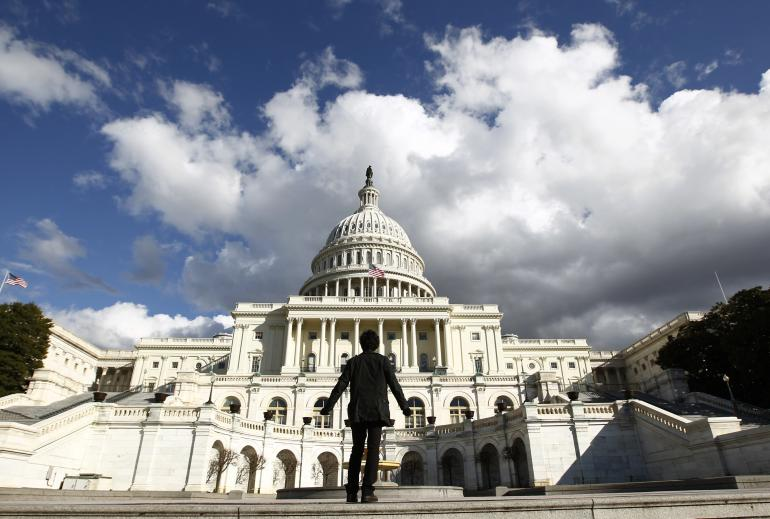 The U.S. Capitol, with a gazing tourist. Image: Reuters.