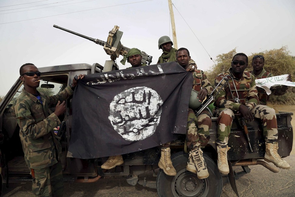 Soldiers from Niger hold up a Boko Haram flag seized in the town of Damasak, Nigeria. [Reuters]