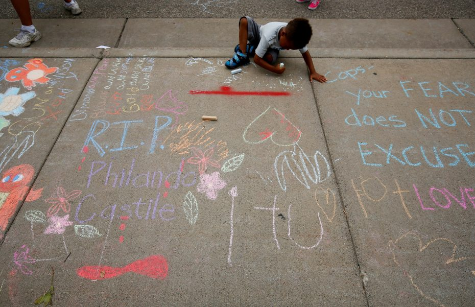 A boy sits near messages written in chalk as demonstrators protesting the shooting death of Philando Castile gather in front of the police department in St Anthony, Minnesota, U.S., July 10, 2016.  REUTERS/Adam Bettcher
