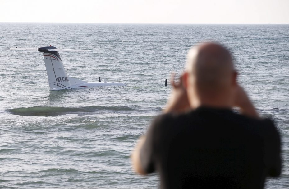 A man takes a photo with his cell phone of an airplane that made an emergency landing in the waters of the Mediterranean sea off the shore of Tel Aviv, Israel, April 3, 2016. REUTERS