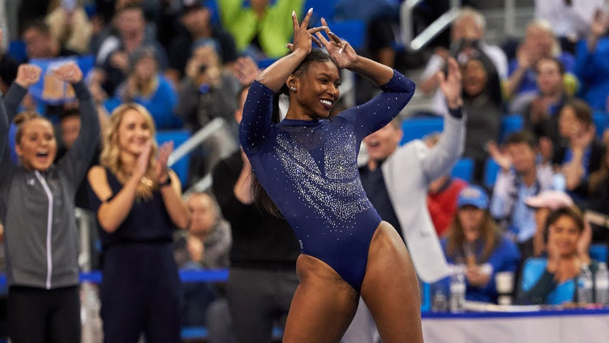young black female gymnast making crown with her fingers in stadium