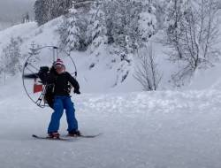 Screenshot of video of skiers using paragliding motors to go up a hill