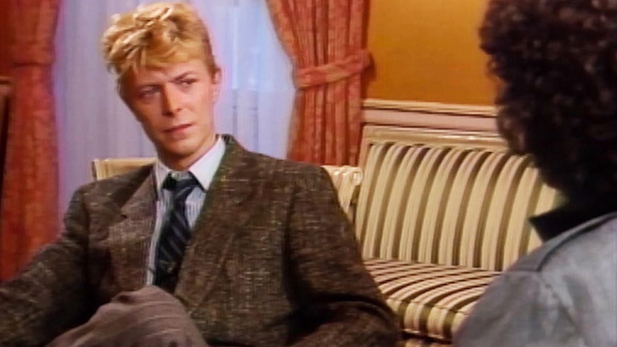 David Bowie sits on a couch