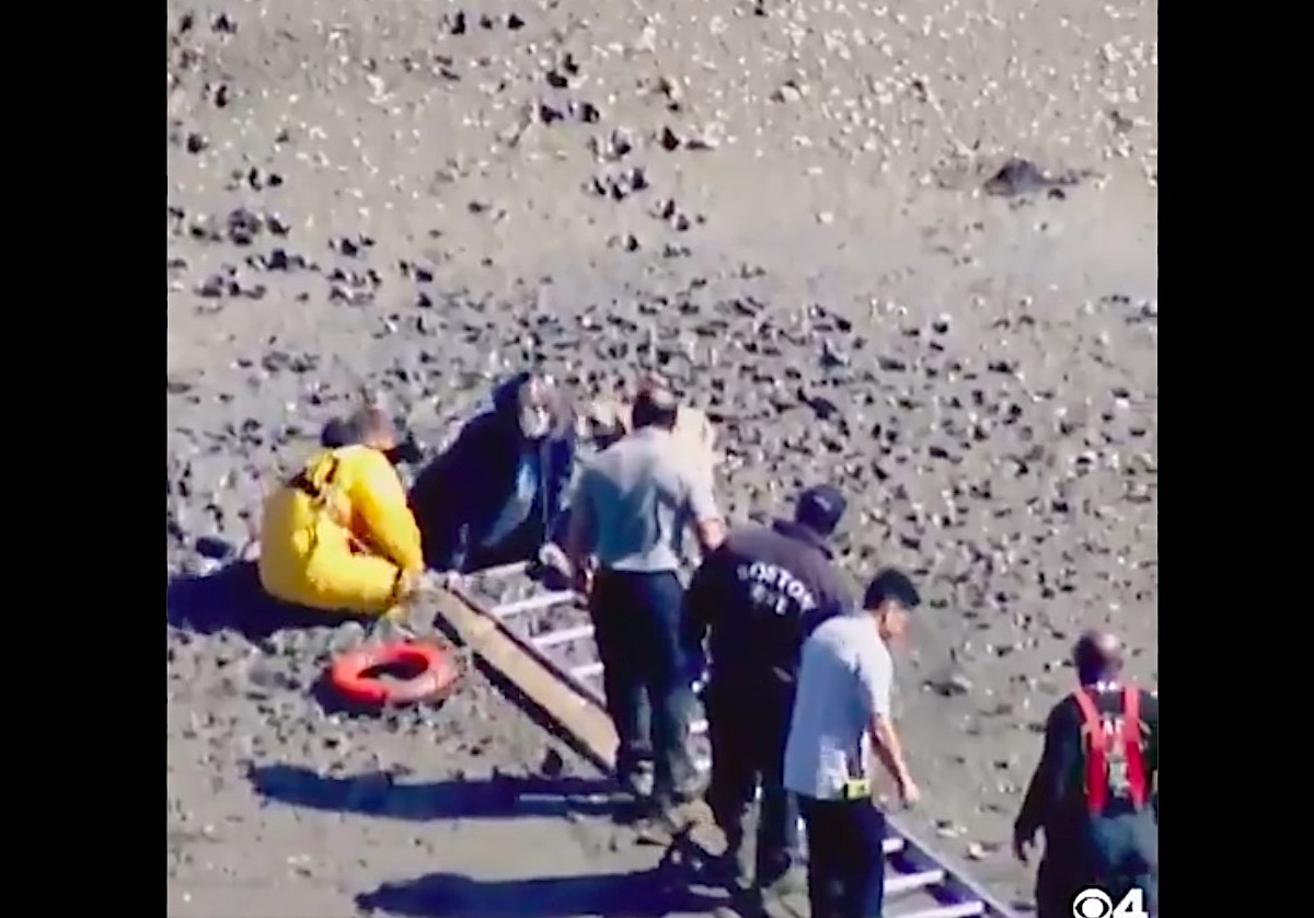 Woman gets trapped in the sand while walking on a Boston beach
