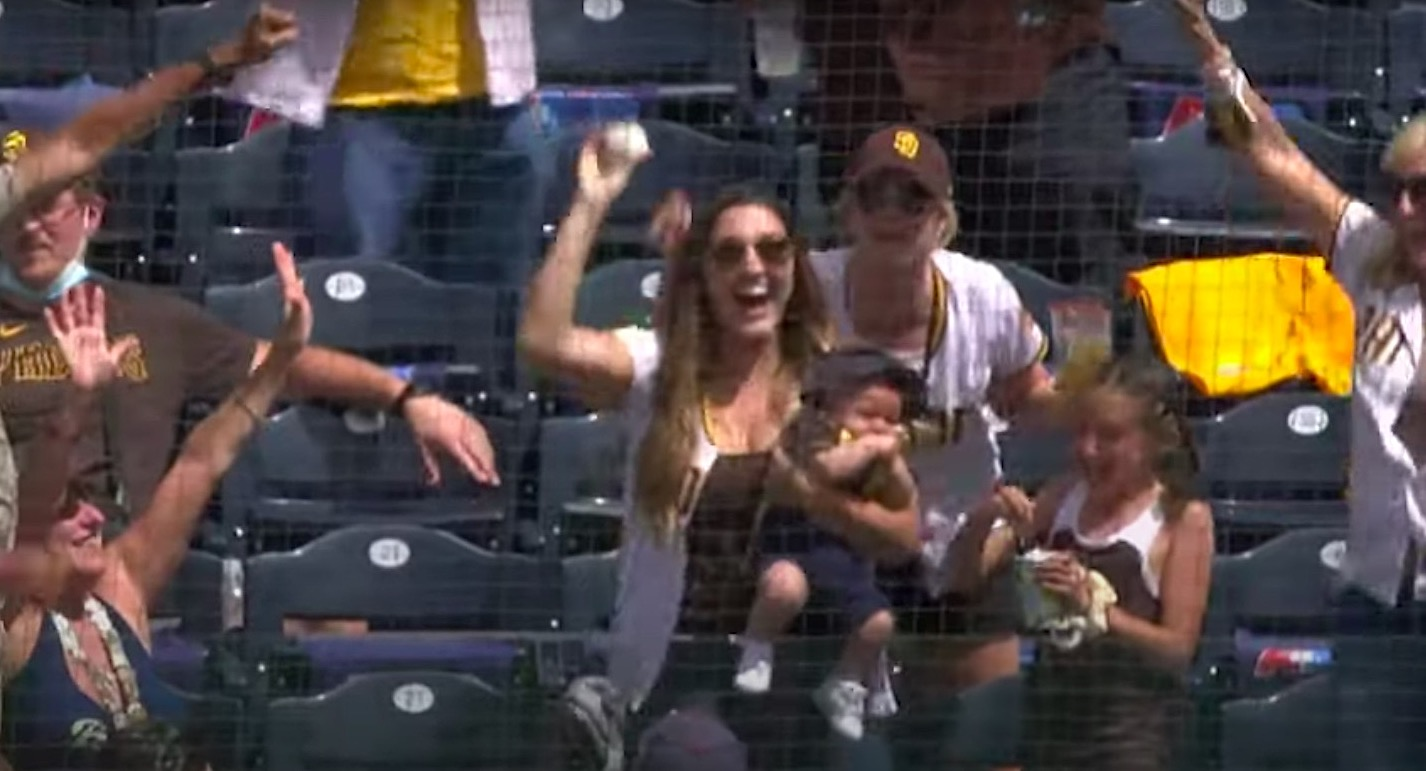 Woman catches a foul ball while holding a baby