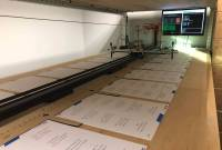 Photo of a robot pen plotter mounted on an 8 foot long piece of plywood