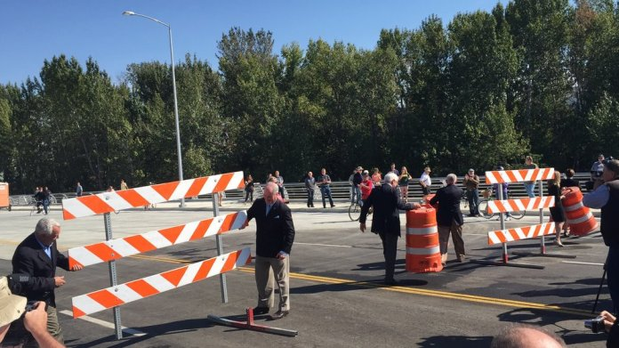 Officials, including Boise mayor Dave Bieter & Boise State president Bob Kustra remove barricades shortly before the bridge opened