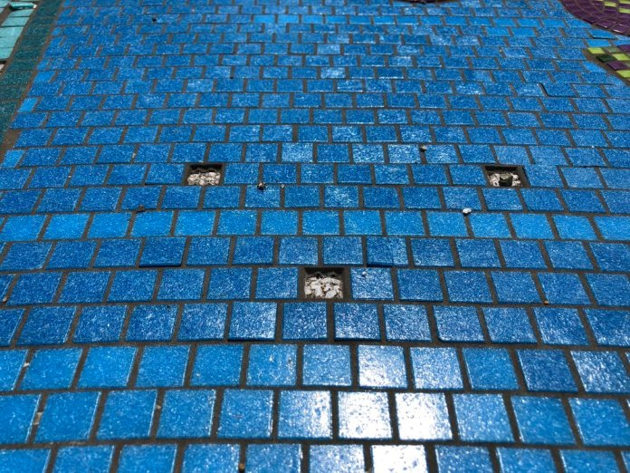 A close view shows tiles that have popped off the surface of the mosaic. Photo: Don Day/BoiseDev.com