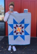 Jill Smith from Ronald McDonald Charities Idaho holding quilt with a large star