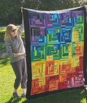 woman holding up a colorful quilt