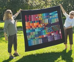 two women holding up modern quilt