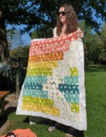 woman holding up multi color quilt