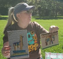 woman holding up quilted postcards