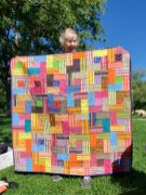 woman holding up a bright quilt