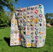 holding up a hexi quilt in the park