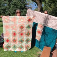 women holding up quilts