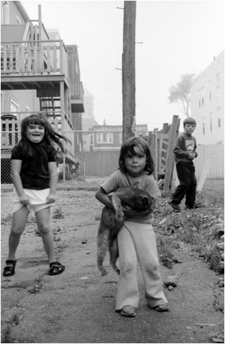 Kids playing on the South End streets in Saint John, New Brunswick. In their imaginative game, they were saving the cat from an imminent danger. The cat seemed to play along.