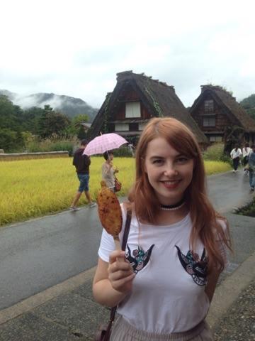 Ingvill, jente med langt hår, som holder en frityrstekt noe på pinne foran japanske hus