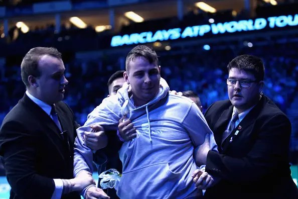 LONDON, ENGLAND - NOVEMBER 19:  A spectator is removed from the arena by security after attempting to get onto the court during the men's singles semi final between Novak Djokovic of Serbia and Kei Nishikori of Japan on day seven of the ATP World Tour Finals at O2 Arena on November 19, 2016 in London, England.  (Photo by Julian Finney/Getty Images)