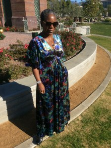 Glenda's maxi dress is a multi colored blue, black, green with touches of pink floral pattern. It has a v-neck, surplice waist and elbow-length kimono sleeves. She is posed standing in front of a circular wall with a floral garden on top.