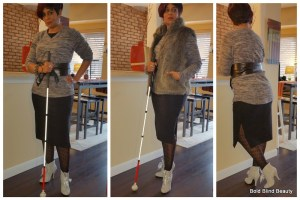 Black midi dress under a gray fleece sweatshirt belted with a black obi belt, black patterned tights and gray booties.