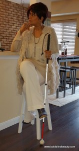 Sitting on my bar stool with my white cane in hand.