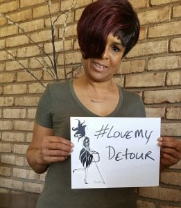 "I'm standing holding a sign that has Abigail and the ""Love My Detour"" hashtag"