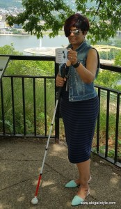 I'm standing with my white cane, holding the mug with Point State Park fountain (Golden Triangle) in the background