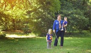 Holly is standing on a lawn holding Aoife in her left arm, with her white cane in her right hand and Nuala standing beside her.