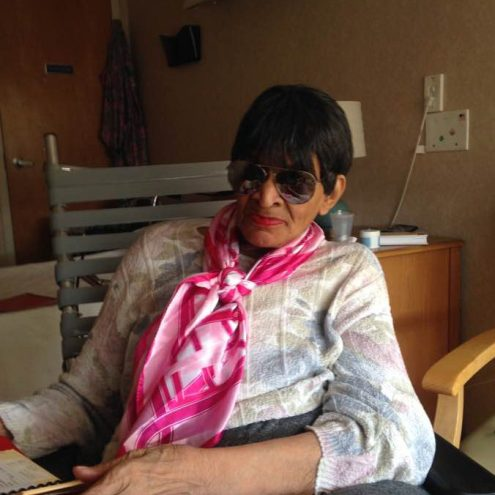 Alzheimer's, Vision Loss, and Caregiving picture of my mom at the nursing home sitting in her wheelchair. She's posing with her sunglasses and a colorful scarf tied around her neck.