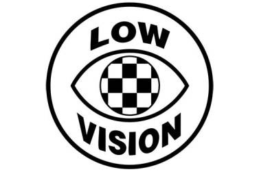 """The Checkered Eye emblem is a simple line drawing of an eye, the center of which, the iris, is black and white checkers. The wearable symbol bears theCheckered Eyeand the text""""LOW VISION"""". It has been translated to French, Spanish, and Thai as well. The background is white, the outline, emblem, and text are black."""