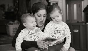 Holly has her two daughters sitting on her lap as she reads a story to them.
