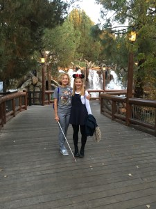 Silvia (white cane in hand) and her daughter (wearing Mickey Mouse ears) are posed standing in Disneyland.