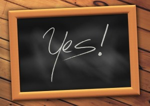 "Wooden framed slate board with the word ""Yes!"""