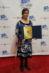 Jo Pinto Receives the 2016 Colorado Independent Publishers Association Award. She is seen here posing for the camera holding her award in both hands with her white cane under her right arm. Jo is looking very stylish in a blue, black & white abstract floral print dress and black boots.