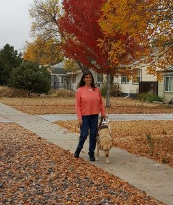 Second photo of Jo with Anlyn walking on the leaf strewn tree-lined sidewalk with gold, red and orange autumn trees.