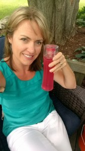 Leslie is smiling for the camera and posing outside near a tree with a clear container of Plexus in her left hand. She is looking summer cool and stylish in a green tank top and white pants.