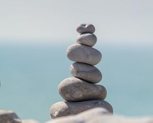 Six assorted stones balanced on top of one another to represent balance.