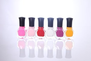 Six generic bottles of nail color in a range of colors from light to dark pink, red, white and yellow.