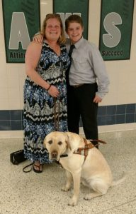 Liz is standing on the left, and Logan standing on her right. They are both dressed up for Logan's chorus concert at school this past May. Her guide dog, Bryce Krispie is sitting in front of her, his nose and face towards the left side of the photo and his rump pointed between her and Logan's feet.