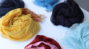 Assorted lightweight colored scarves balled up on a white table