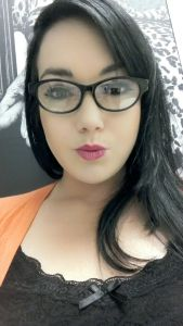 In this selfie of Eileen she is wearing a black lace cami under an orange sherbert colored cardigan. As in her featured photo she is wearing dark-framed eyeglasses and her long dark hair frames her pretty face.