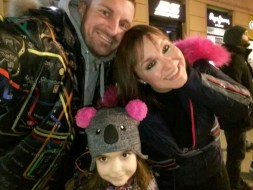 Selfie of Ivana, her husband and daughter hamming it up for the camera. Their little girl is wearing an adorable gray koahla bear hat with pink puff ball ears. Ivana and her hubby are both wearing winter jackets and it looks like they are in a cafe or fast food restaurant.
