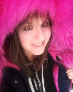 In this photo Ivana is smiling and she has a bright fucshia furry hood on her head. Her brown hair frames her lovely face. Her winter jacket is black and trimmed in bright fuschia.