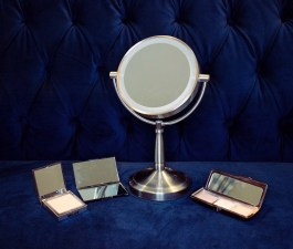 Image description: three compact mirrors and a standing desk mirror on a blue velvet sofa.