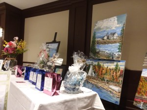 Three of Diane Krek's landscape paintings are on easels behind a banquet table with Chinese Auction and Silent Auction items. In front of each auction item is a pink or blue foil gift bag for the raffle tickets.