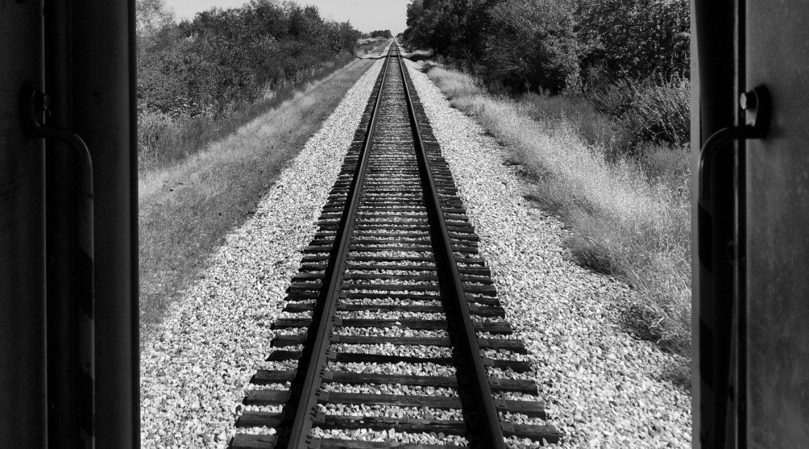 A black & white image of a long stretch of railroad track taken from the caboose.