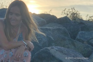 Featured image shows Victoria sitting on a large rock on the beach as the sun sets behind her